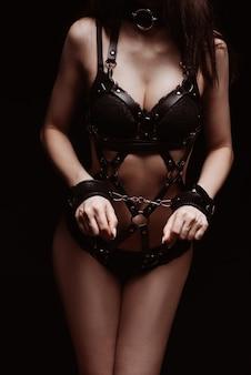 Bdsm. ragazza in manette e intimo sexy in pelle nera