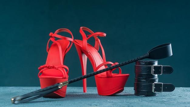 Completo bdsm per giochi di sesso per adulti. scarpe rosse di striptease col tacco alto e manette, frusta su sfondo scuro
