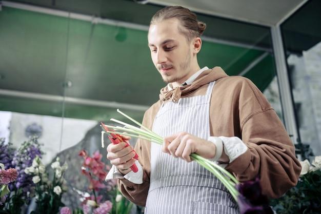 Sii attento. fiorista felice positivo utilizzando attrezzature da giardinaggio durante il taglio degli steli