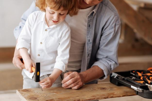 Stai attento. piccolo aiutante in piedi vicino a suo padre e chinando la testa mentre tiene il martello in mano Foto Premium