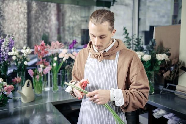 Essere consapevole. persona di sesso maschile concentrata che preme le labbra mentre prepara i fiori per ikebana