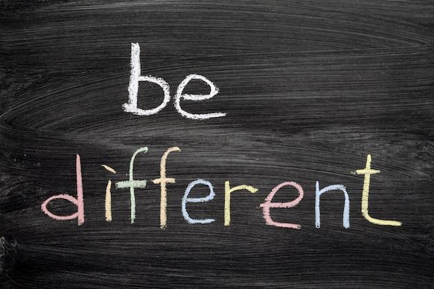 Essere una frase diversa scritta a mano sulla lavagna della scuola