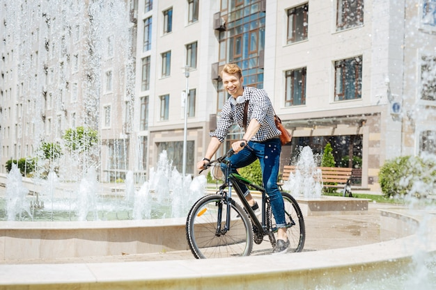 Non essere in ritardo. felice gioioso uomo che cavalca veloce sulla sua bicicletta