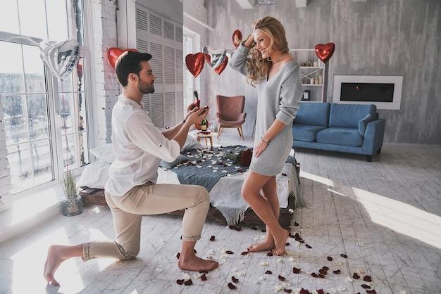 Sii mio per sempre! giovane donna sorpresa che guarda l'anello di fidanzamento con un sorriso mentre il suo ragazzo è inginocchiato in camera da letto