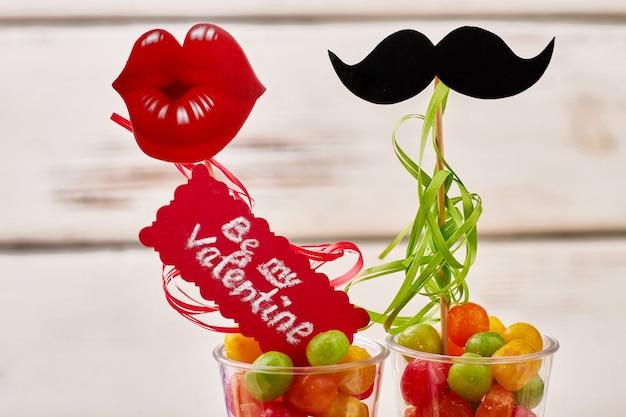 Sii la mia iscrizione di san valentino. labbra, mustage, caramelle e biglietto di auguri. sapere come chiederle.