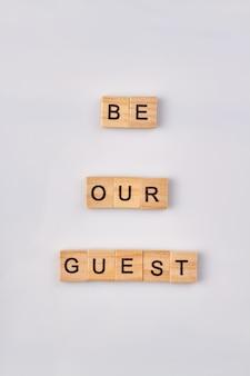 Sii nostro ospite parole di legno. isolato su sfondo bianco.