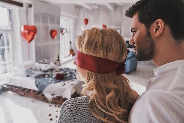 Essere pazientare. vista posteriore della giovane donna in piedi con gli occhi bendati con il suo ragazzo mentre trascorre del tempo a casa