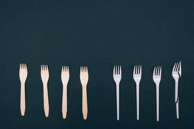 Sii privo di plastica. zero sprechi. forchette ecologiche naturali monouso in fila, vista dall'alto. ridurre riutilizzare riciclare. prodotto monouso in plastica o riciclabile riutilizzabile