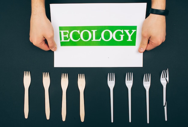 Sii privo di plastica. zero sprechi. le mani tengono la carta con la parola ecologia vicino alle forcelle naturali e monouso ecologiche. le forcelle sono in fila su sfondo scuro, vista dall'alto. ridurre riutilizzare riciclare.