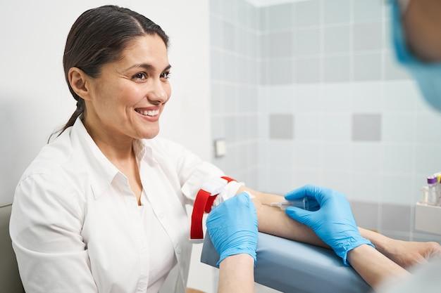 Sii positivo. gentile giovane paziente che mantiene il sorriso sul viso mentre fa il pugno durante il prelievo di sangue