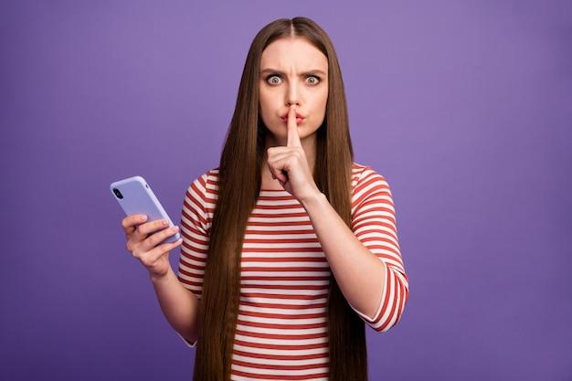 Stai zitto, non condividere! la ragazza seria della gioventù usa lo smartphone ha la comunicazione di social media privata mostra senza voce segno le labbra del dito indice indossano il ponticello a strisce bianco isolato parete di colore viola