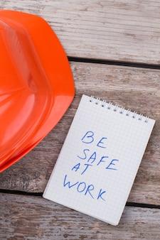 Essere al sicuro sul concetto di lavoro. casco da muratore con blocco note sul tavolo invecchiato.