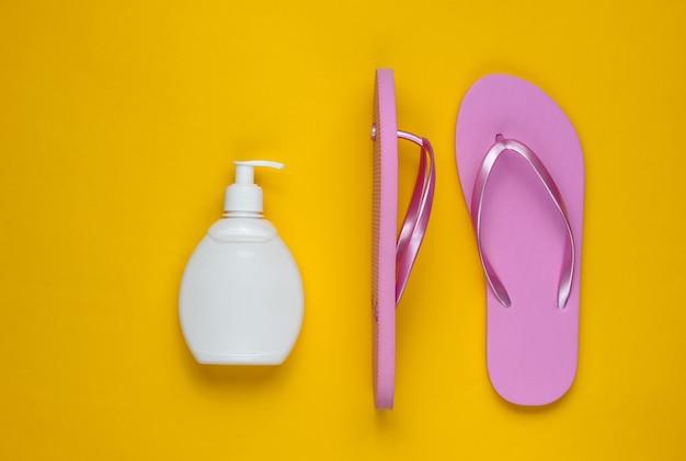 Accessori da spiaggia. infradito rosa spiaggia alla moda, bottiglia di protezione solare su sfondo di carta gialla. lay piatto. vista dall'alto