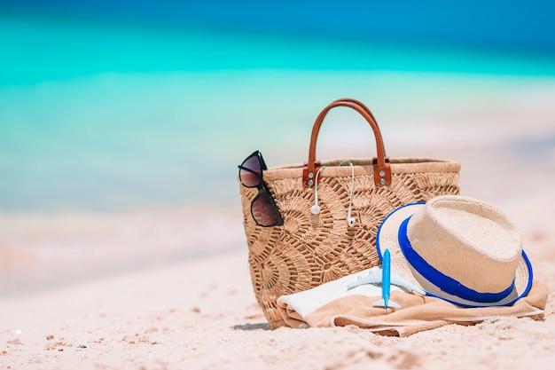 Accessori da spiaggia: borsa di paglia, cappello e occhiali da sole sulla spiaggia