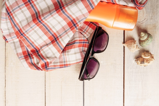 Accessori da spiaggia su tavola di legno bianca composizione piatta vista dall'alto. crema solare, occhiali da sole, cappello estivo, conchiglie.