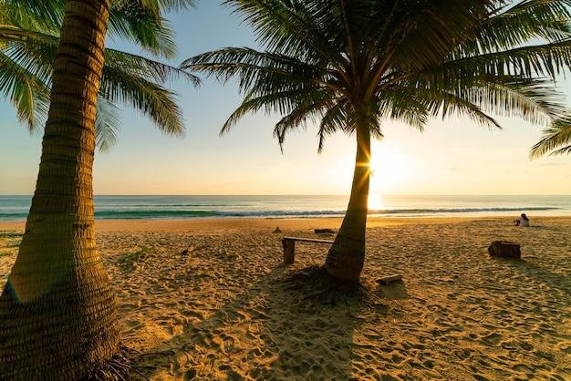 Fondo del concetto di vacanze autunnali della spiaggia cornice della natura con palme da cocco sulla spiaggia con luce del sole bagliore bellissimo tramonto o alba sullo sfondo del paesaggio.