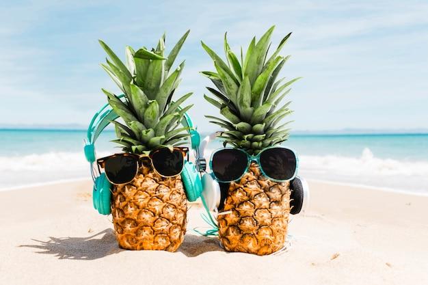 Sfondo spiaggia con ananas indossando occhiali da sole
