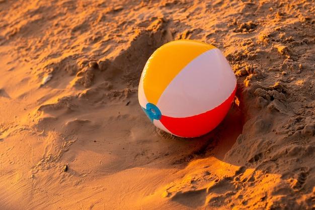 Pallone da spiaggia in riva al mare al caldo tramonto