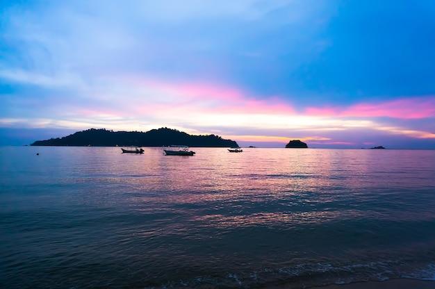 Spiaggia, bel tramonto viola sul mare con colline