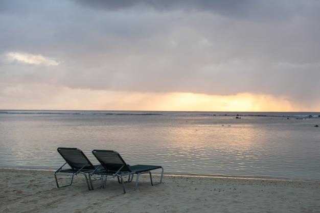 Sedia a sdraio sulla spiaggia con il tramonto