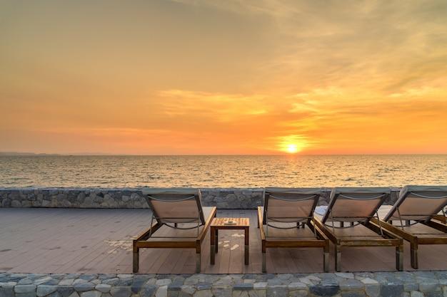 Tramonto della sedia della spiaggia con lo spazio della copia