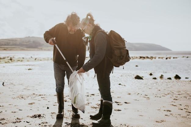 Volontari per la pulizia della spiaggia che raccolgono la spazzatura per la campagna ambientale