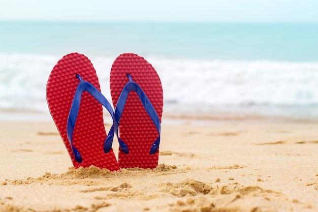 Infradito da spiaggia in fantasia di colore rosso su sabbia tropicale