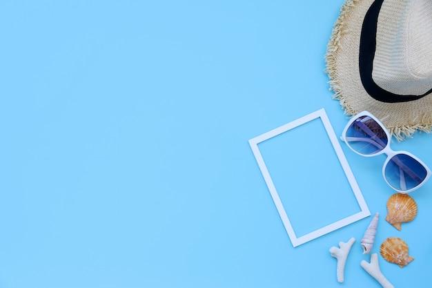 Cappello da spiaggia, occhiali, cornice e shellson sfondo blu in estate asia, copia spazio, vista dall'alto, stile minimal