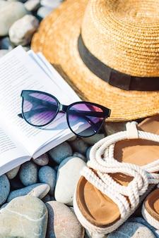 Cappello da spiaggia sul libro aperto con crema solare e scarpe sulla spiaggia di ciottoli