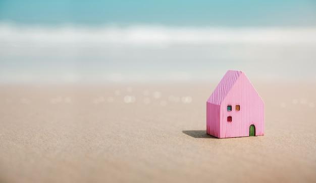 Concetto di casa al mare. mini casa in legno sulla spiaggia di sabbia destinazione per le vacanze o la vita in pensione