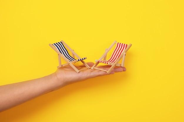 Lettini da spiaggia a portata di mano, concetto di vacanza estiva, lettini su sfondo giallo