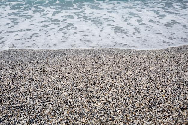 La spiaggia della costa mediterranea con onde di acqua azzurra. brezza marina estiva