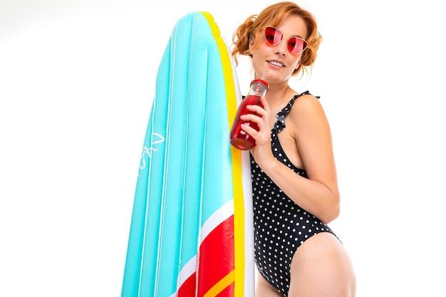 Concetto di festa in spiaggia, la ragazza beve un cocktail in un costume da bagno retrò e tiene una tavola da surf.