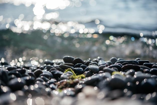 Ciottoli da spiaggia con scintillanti bokeh di sole e onde del mare spumeggianti