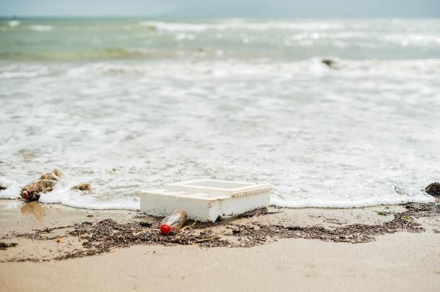 Inquinamento da spiaggia. bottiglie di plastica e altri rifiuti sulla spiaggia del mare