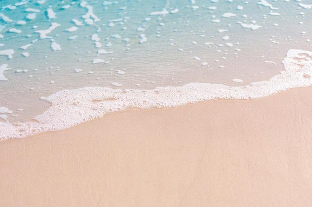 La spiaggia e la sabbia con l'acqua blu e l'onda spumeggiante nella spiaggia tropicale in thailandia