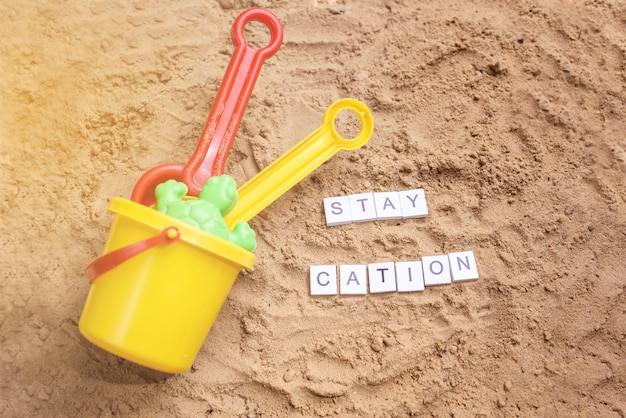 Sabbia da spiaggia con giocattoli per il bambino, acqua, la parola holi rimane in lettere colorate.