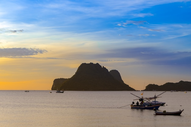 Spiaggia, mare durante la stagione estiva all'alba del mattino con la barca da pesca sagoma.