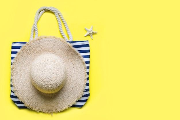 Borsa da spiaggia a righe cappello di paglia e conchiglia su sfondo giallo