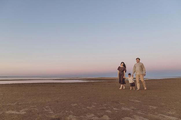 Alba sulla spiaggia con la famiglia e il cane che camminano lungo la spiaggia. vestiti di lino dall'aspetto familiare. copia spazio.