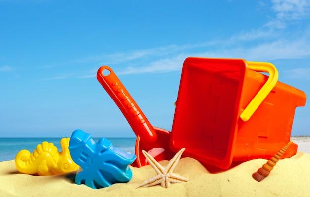 Tiri i giocattoli in secco nella fine della sabbia in su, vita di spiaggia