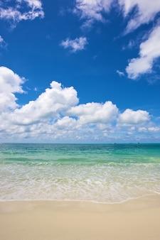 Spiaggia e mare tropicale sotto il cielo azzurro brillante al giorno d'estate