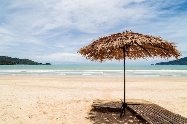 Ombrellone fatto di foglie di palma su una perfetta spiaggia bianca di fronte al mare a patong beach