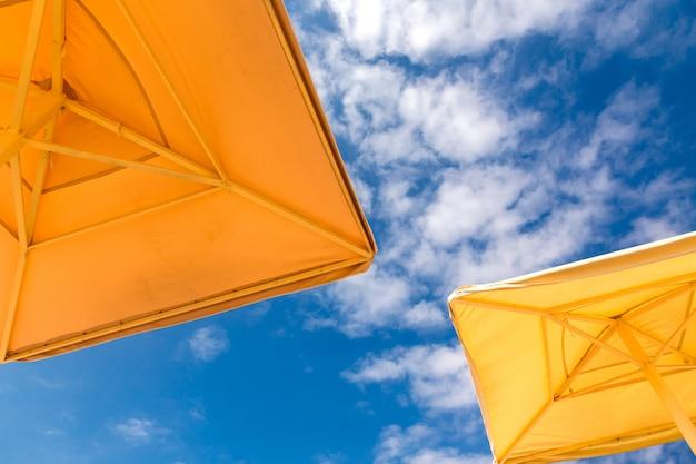 Ombrelloni su uno sfondo blu cielo nuvoloso