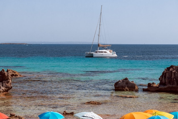 Ombrelloni sulla riva e un catamarano bianco nel mare al largo dell'isola di ibiza