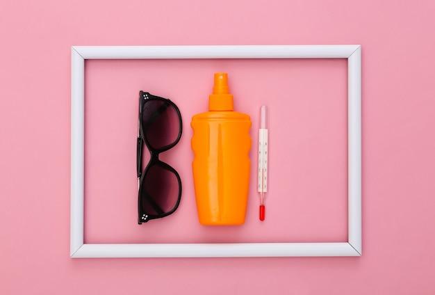 Vacanza al mare. estate. bottiglia sunblock, occhiali da sole e termometro su rosa con cornice bianca