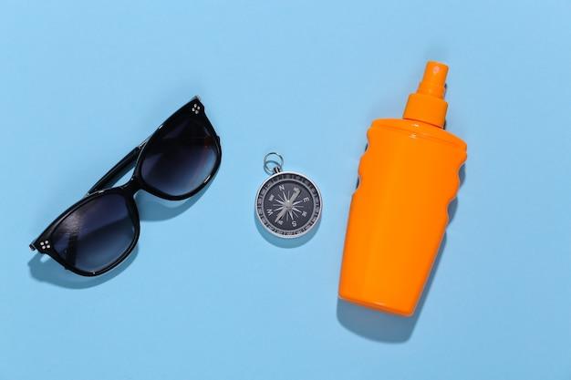 Vacanza al mare, concetto di viaggio. bottiglia sunblock, bussola e occhiali da sole su blu brillante