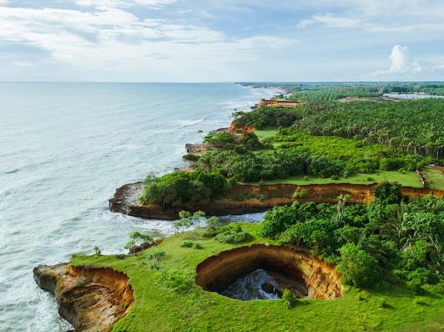 Spiaggia vista dall'aria con un bellissimo mare blu e una bella foresta verde e un buco a forma di cuore sulla costa indonesiana