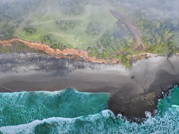 Vista della spiaggia dall'aria con onde calme durante il giorno nel nord bengkulu, indonesia