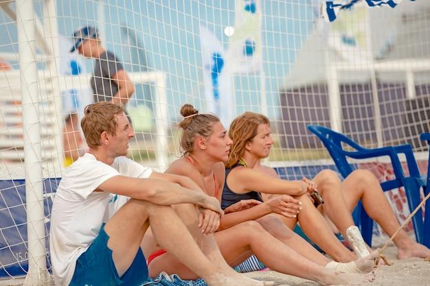 Beach volley. sfera del gioco sotto luce solare e cielo blu. un gruppo di giocatori di pallavolo in attesa di giocare sulla spiaggia